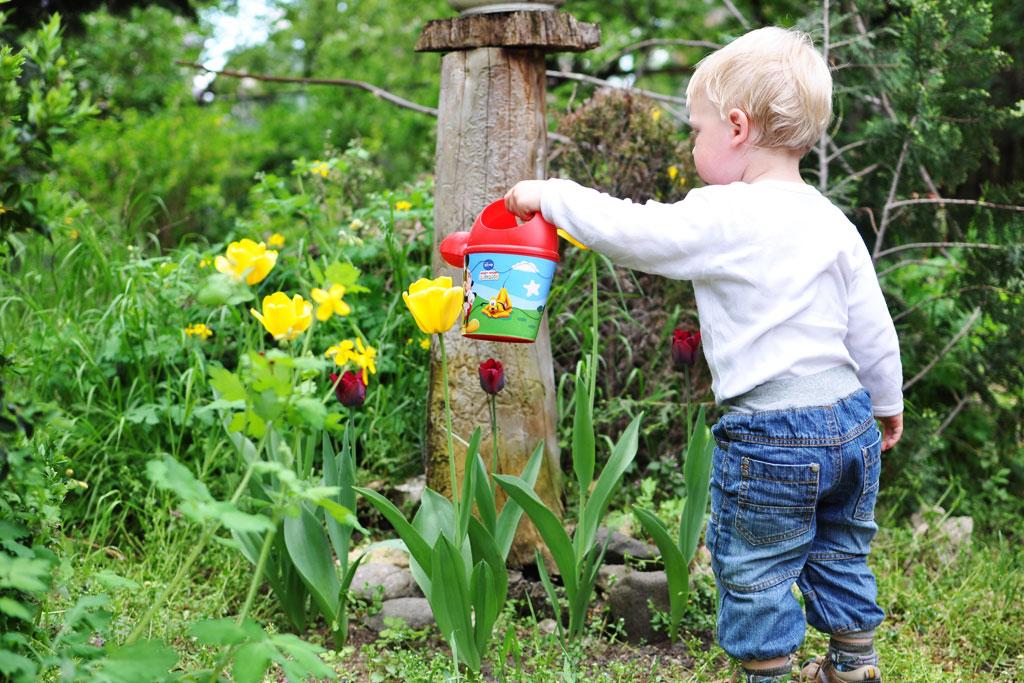 Kind die water geeft aan bloemen in de tuin